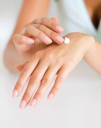 A photo of someone applying body lotion to a hand.