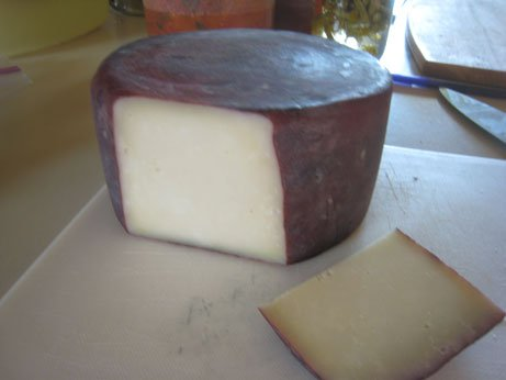 Photo of pinot noir cheese with a slice laying beside the cheese