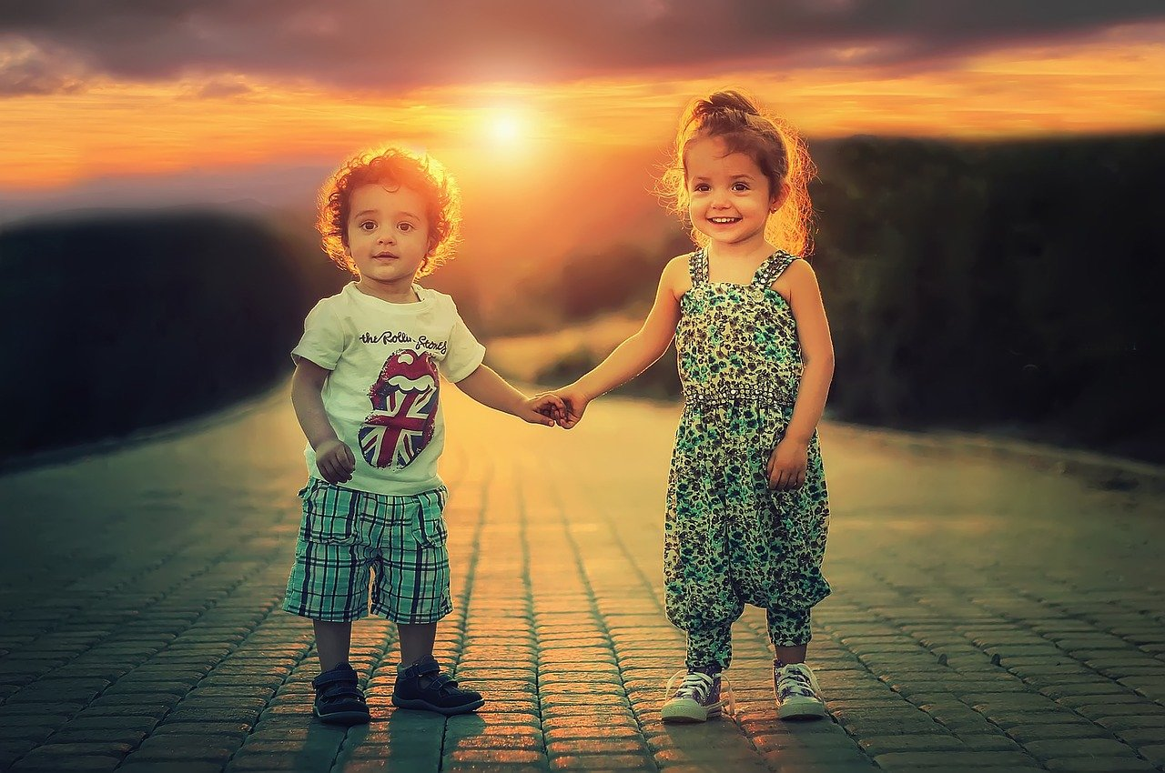 A photos of two smiling children holding hands in the sun.