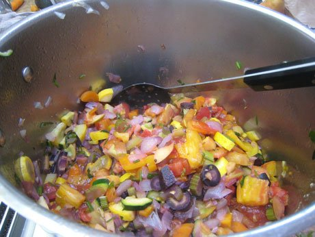 Colorful vegetables cooking in large pot.