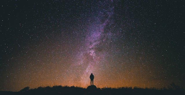 A photo of a person standing alone under the galaxy of stars in the night.