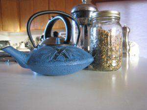 Photo of blue, iron tea pot, tea press and herbal tea in jar.