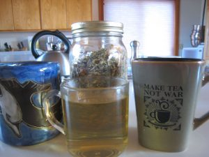 Photo of a cup of herbal tea with dry herbs in a jar.