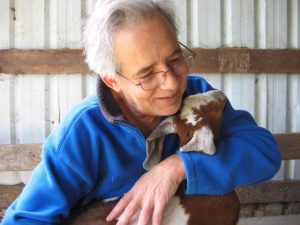 Photo of a man smiling as he looks at a baby goatling in his lap.