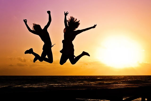 A photo of two people jumping in the air at sunset.