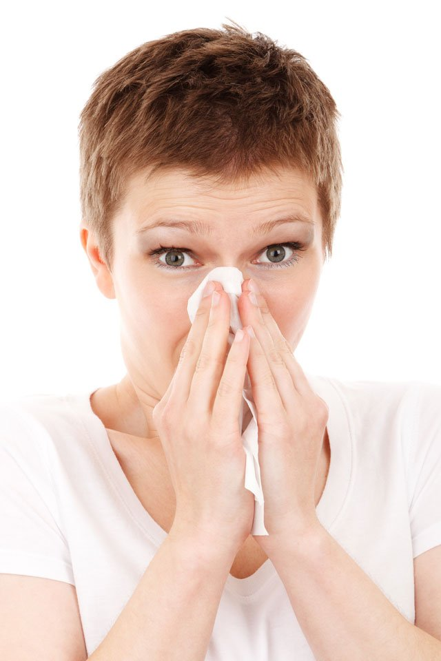 Photo of a woman holding a tissue to her nose.
