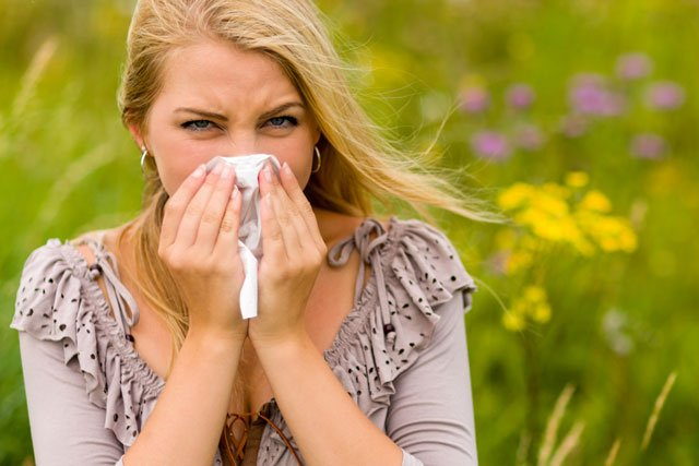 Photo of a woman with a field behind her, a hanky to her face, experiencing hay fever.