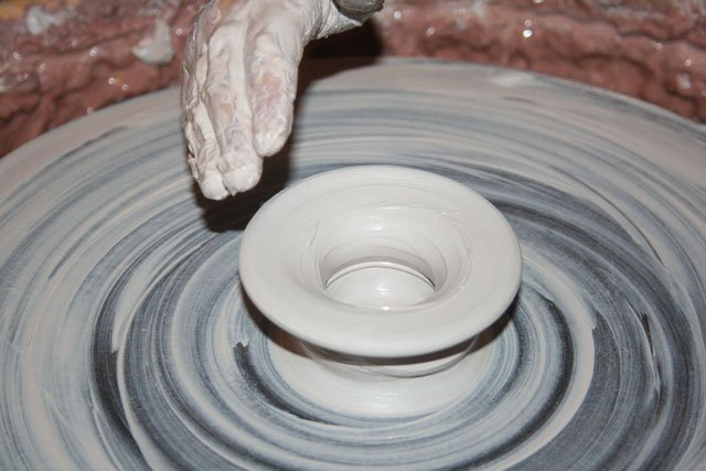 A photo of clay being worked on a wheel.