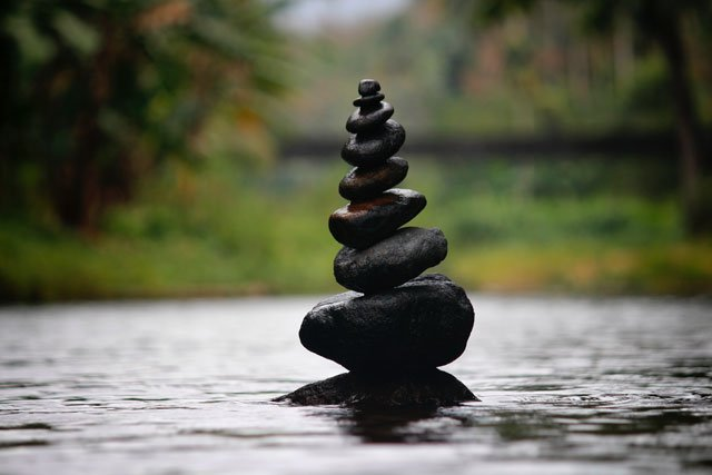 A stack of rocks resting in the water.