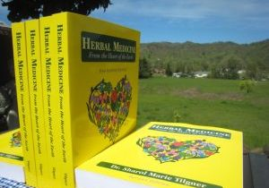 Photo of Herbal Medicine books with field and mountains in background.