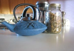 Photo of blue, iron tea pot, tea press and herbal tea in jar.